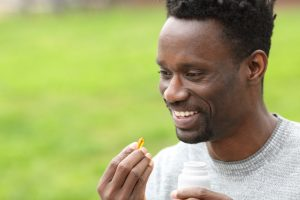 african american man taking vitamin in the park