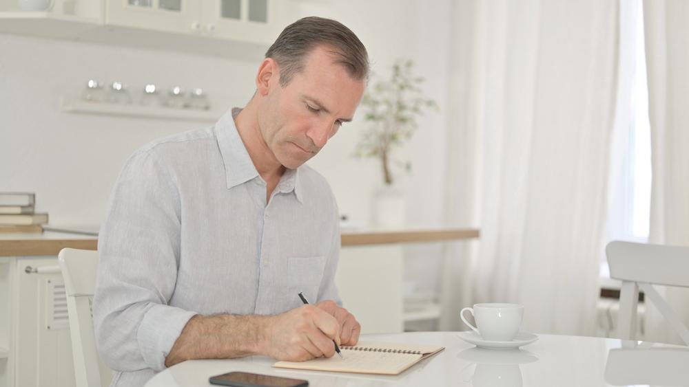 man journaling at kitchen table