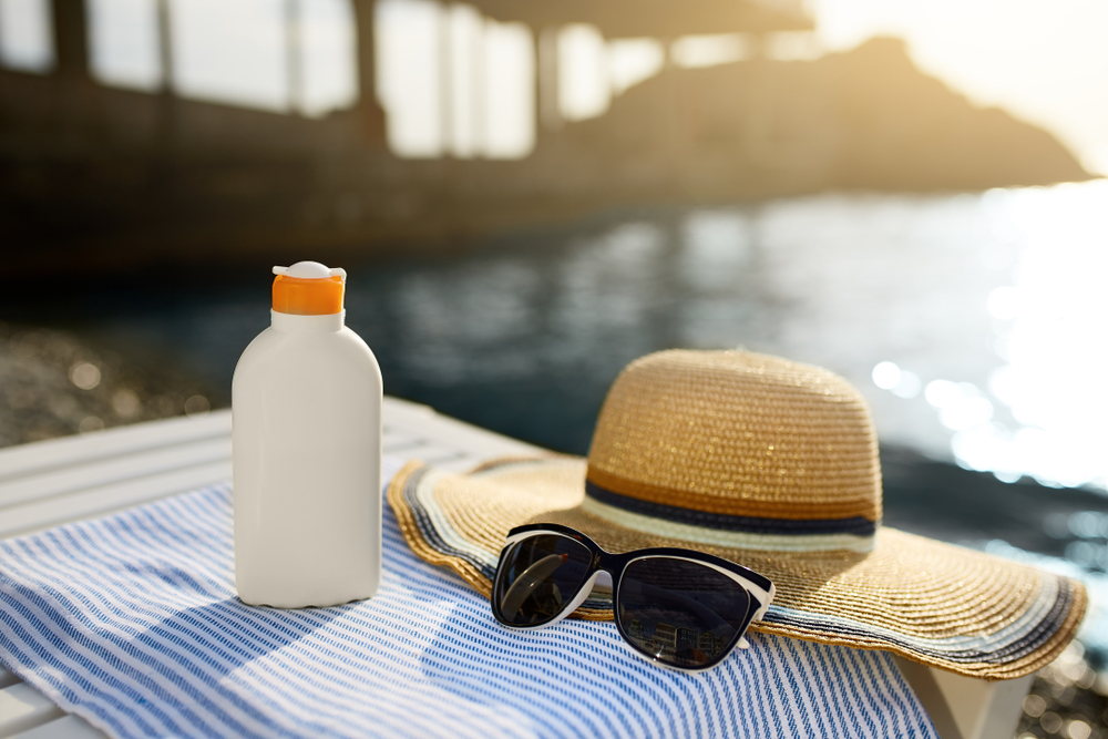 sunscreen bottle, straw hat and sunglasses near the water
