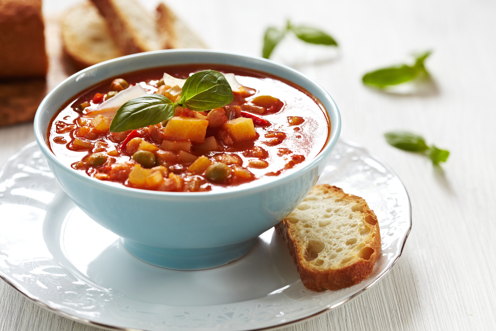 minestrone soup in bowl with slice of bread on the side