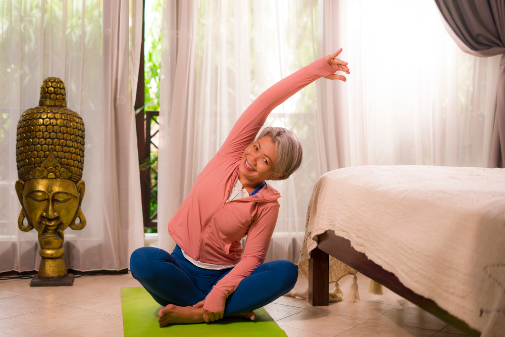 asian woman stretching in her home