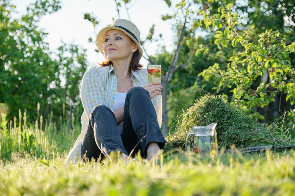 woman relaxing in her garden drinking lemonade
