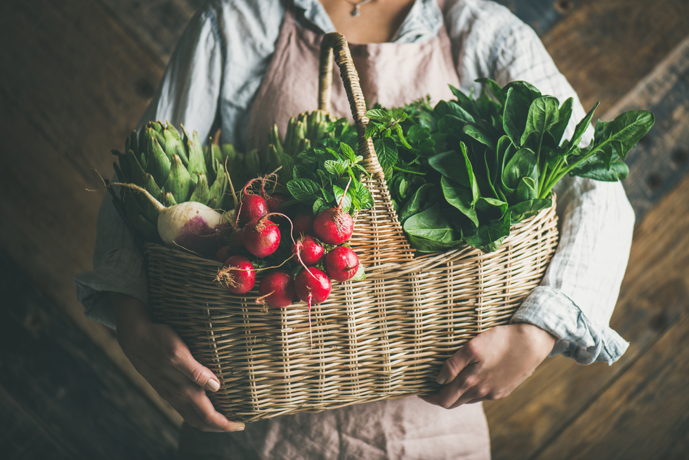 woman holding leafy greens in a basket
