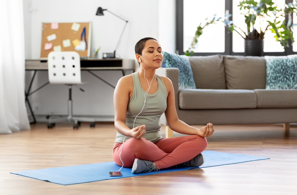 young black woman using a meditation app at home